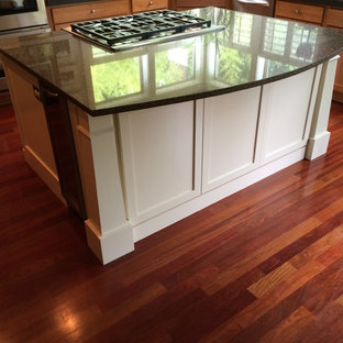 Design ideas for a medium sized traditional l-shaped enclosed kitchen in Portland with shaker cabinets, white cabinets, granite worktops, medium hardwood flooring, an island, red floors and stainless steel appliances.