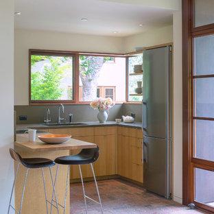 サンフランシスコの小さいモダンスタイルのおしゃれなキッチン (フラットパネル扉のキャビネット、グレーのキッチンパネル、レンガの床、アンダーカウンターシンク、淡色木目調キャビネット、コンクリートカウンター、石スラブのキッチンパネル、シルバーの調理設備の、赤い床) の写真