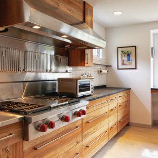 フィラデルフィアの中サイズのインダストリアルスタイルのおしゃれなキッチン (ステンレスカウンター、インセット扉のキャビネット、中間色木目調キャビネット、ベージュキッチンパネル、セラミックタイルのキッチンパネル、シルバーの調理設備の) の写真