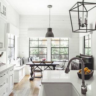 Idée de décoration pour une cuisine américaine champêtre avec un évier de ferme, un placard avec porte à panneau encastré, des portes de placard blanches, une crédence blanche, une crédence en carrelage métro, un sol en bois brun et un îlot central.