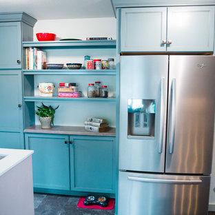Idee per una cucina parallela vittoriana chiusa e di medie dimensioni con lavello da incasso, ante lisce, ante blu, top in laminato, paraspruzzi grigio, paraspruzzi in gres porcellanato, elettrodomestici in acciaio inossidabile, pavimento in vinile e nessuna isola