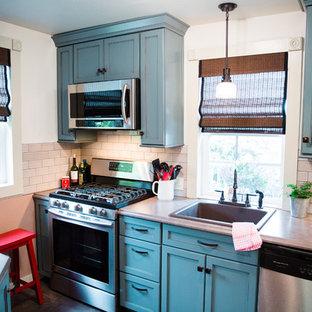 シアトルの中サイズのヴィクトリアン調のおしゃれなキッチン (ドロップインシンク、フラットパネル扉のキャビネット、青いキャビネット、ラミネートカウンター、グレーのキッチンパネル、磁器タイルのキッチンパネル、シルバーの調理設備の、クッションフロア、アイランドなし) の写真