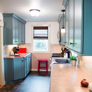 Foto di una cucina parallela vittoriana chiusa e di medie dimensioni con lavello da incasso, ante lisce, ante blu, top in laminato, paraspruzzi grigio, paraspruzzi in gres porcellanato, elettrodomestici in acciaio inossidabile, pavimento in vinile e nessuna isola