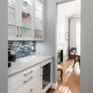 Modelo de cocina comedor en L, moderna, grande, con armarios con paneles lisos, puertas de armario blancas, encimera de cuarzo compacto, salpicadero azul, suelo de madera clara, suelo beige y encimeras blancas