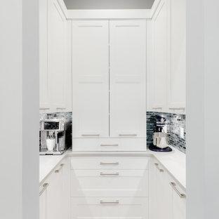 Imagen de cocina en U, minimalista, pequeña, con armarios con paneles lisos, puertas de armario blancas, encimera de cuarzo compacto, salpicadero azul, electrodomésticos de acero inoxidable, suelo de madera clara, una isla, suelo beige, encimeras blancas y despensa