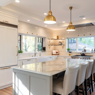 Inspiration for a transitional l-shaped medium tone wood floor and brown floor kitchen remodel in Salt Lake City with a farmhouse sink, recessed-panel cabinets, white cabinets, white backsplash, subway tile backsplash, stainless steel appliances, an island and white countertops