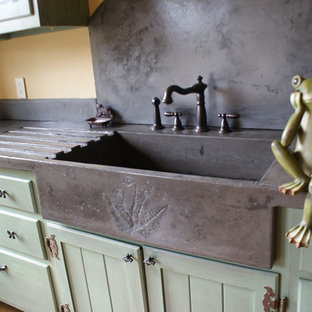 Photo of an eclectic kitchen in Charlotte with an integrated sink, green cabinets and concrete benchtops.