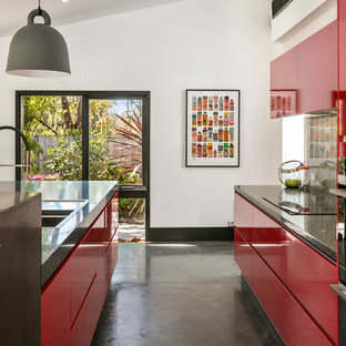 Photo of a contemporary galley kitchen in Sydney with a double-bowl sink, flat-panel cabinets, red cabinets, grey splashback, concrete floors, with island, grey floor and grey benchtop.
