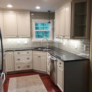 ボルチモアの小さいトラディショナルスタイルのおしゃれなキッチン (アンダーカウンターシンク、レイズドパネル扉のキャビネット、白いキャビネット、御影石カウンター、グレーのキッチンパネル、セラミックタイルのキッチンパネル、シルバーの調理設備の、濃色無垢フローリング、アイランドなし、赤い床) の写真