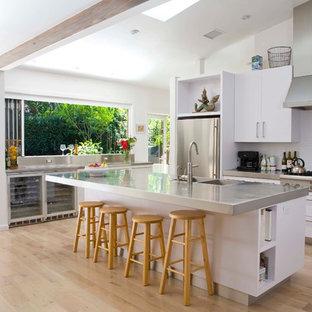 Zweizeilige, Offene Moderne Küche mit flächenbündigen Schrankfronten, weißen Schränken, Edelstahl-Arbeitsplatte, Küchengeräten aus Edelstahl und integriertem Waschbecken in Los Angeles