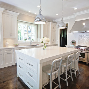 Large trendy u-shaped dark wood floor eat-in kitchen photo in Chicago with an undermount sink, shaker cabinets, white cabinets, white backsplash, subway tile backsplash, stainless steel appliances, solid surface countertops, an island and white countertops