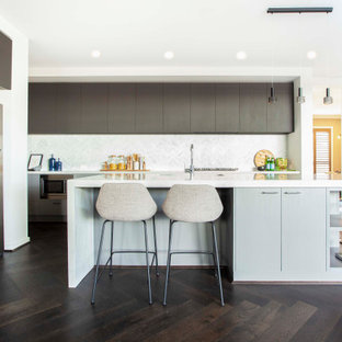 Contemporary l-shaped kitchen in Melbourne with an undermount sink, dark wood cabinets, quartz benchtops, white splashback, ceramic splashback, painted wood floors, with island, brown floor and white benchtop.
