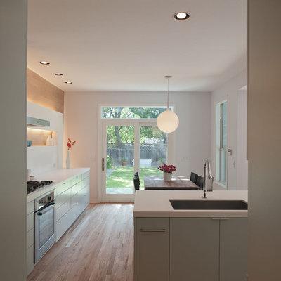 Minimalist eat-in kitchen photo in Austin with a single-bowl sink, flat-panel cabinets, green cabinets, quartz countertops, white backsplash and stone slab backsplash