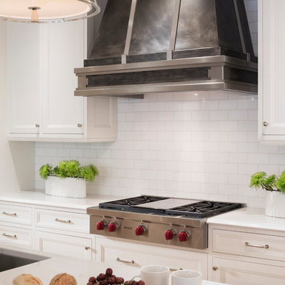 Inspiration for a large transitional l-shaped light wood floor eat-in kitchen remodel in Minneapolis with subway tile backsplash, paneled appliances, an island, a farmhouse sink, recessed-panel cabinets, white cabinets, quartzite countertops and white backsplash