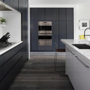 Esempio di una cucina minimal di medie dimensioni con ante lisce, un'isola, lavello sottopiano, ante nere, top in quarzite, elettrodomestici da incasso, pavimento in legno massello medio e pavimento grigio
