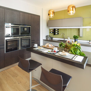 Photo of a medium sized contemporary l-shaped kitchen/diner in Oxfordshire with a single-bowl sink, flat-panel cabinets, dark wood cabinets, engineered stone countertops, green splashback, glass sheet splashback, stainless steel appliances, light hardwood flooring, an island, brown floors and brown worktops.