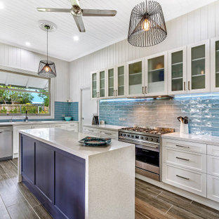 This is an example of a beach style l-shaped kitchen in Brisbane with an undermount sink, glass-front cabinets, white cabinets, blue splashback, subway tile splashback, stainless steel appliances, with island, brown floor, grey benchtop and timber.