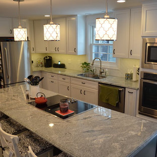 Eat-in kitchen - mid-sized traditional l-shaped dark wood floor eat-in kitchen idea in Bridgeport with an undermount sink, flat-panel cabinets, white cabinets, granite countertops, white backsplash, cement tile backsplash and stainless steel appliances