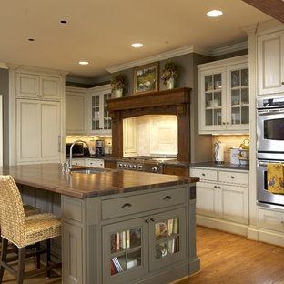 Traditional kitchen remodeling - Kitchen - traditional kitchen idea in Birmingham with beaded inset cabinets, paneled appliances, wood countertops, beige cabinets and brown countertops