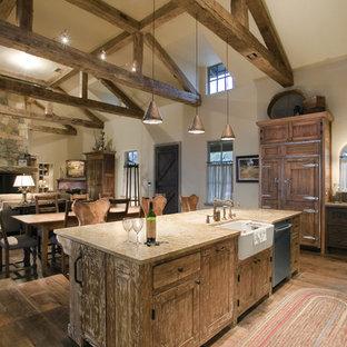 Modelo de cocina en L, rústica, grande, abierta, con encimera de granito, fregadero sobremueble, puertas de armario con efecto envejecido, electrodomésticos con paneles y una isla