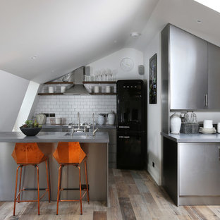 Contemporary kitchen remodeling - Inspiration for a contemporary dark wood floor kitchen remodel in London with flat-panel cabinets, stainless steel cabinets, stainless steel countertops, white backsplash, subway tile backsplash, stainless steel appliances and a peninsula