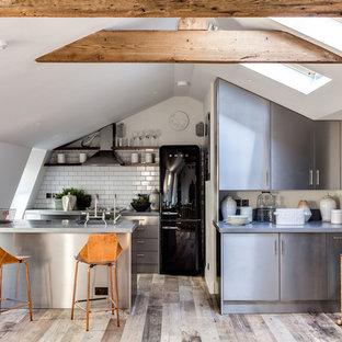 Inspiration för små industriella parallellkök, med släta luckor, skåp i rostfritt stål, vitt stänkskydd, stänkskydd i tunnelbanekakel, svarta vitvaror och en halv köksö