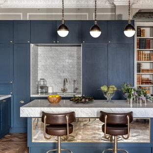 Ejemplo de cocina comedor clásica renovada con armarios estilo shaker, una isla, puertas de armario azules, encimera de mármol, salpicadero verde, salpicadero de azulejos de piedra, fregadero bajoencimera y suelo de madera en tonos medios
