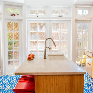This is an example of an eclectic galley kitchen in Philadelphia with a farmhouse sink, beige cabinets, white splashback, coloured appliances, cement tiles, blue floor and white benchtop.