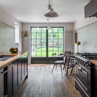 Mid-sized traditional galley eat-in kitchen in London with a double-bowl sink, black cabinets, wood benchtops, white splashback, subway tile splashback, black appliances, medium hardwood floors, shaker cabinets and no island.