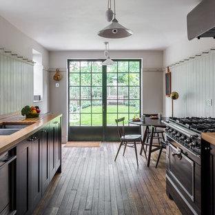 Medium sized victorian galley kitchen/diner in London with a double-bowl sink, black cabinets, wood worktops, white splashback, metro tiled splashback, black appliances, medium hardwood flooring, shaker cabinets and no island.