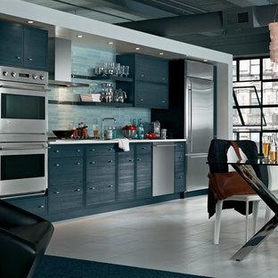 ボストンの中サイズのモダンスタイルのおしゃれなキッチン (アンダーカウンターシンク、フラットパネル扉のキャビネット、青いキャビネット、人工大理石カウンター、青いキッチンパネル、ガラスタイルのキッチンパネル、シルバーの調理設備の、磁器タイルの床、アイランドなし、ベージュの床) の写真