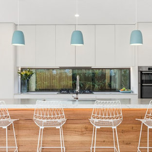 Large contemporary galley eat-in kitchen in Geelong with stainless steel appliances, medium hardwood floors, with island, brown floor, white benchtop, an undermount sink, flat-panel cabinets, white cabinets and window splashback.
