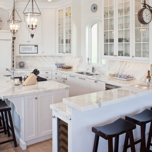 Kitchen - traditional kitchen idea in Tampa with a double-bowl sink, shaker cabinets, white cabinets, white backsplash, paneled appliances and marble backsplash
