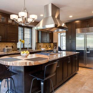 Foto di un'ampia cucina stile americano con lavello sottopiano, ante in stile shaker, ante in legno bruno, top in granito, paraspruzzi marrone, paraspruzzi con piastrelle di vetro, elettrodomestici in acciaio inossidabile, pavimento con piastrelle in ceramica e isola