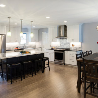 Huge traditional eat-in kitchen ideas - Eat-in kitchen - huge traditional l-shaped laminate floor and gray floor eat-in kitchen idea in Minneapolis with a farmhouse sink, recessed-panel cabinets, white cabinets, quartz countertops, multicolored backsplash, glass tile backsplash, stainless steel appliances and an island