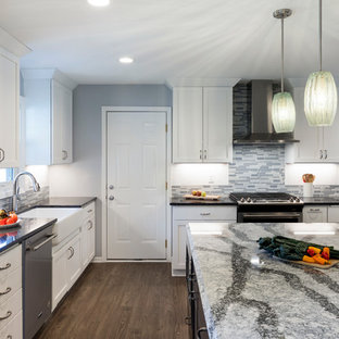 Huge traditional eat-in kitchen appliance - Example of a huge classic l-shaped laminate floor and gray floor eat-in kitchen design in Minneapolis with a farmhouse sink, recessed-panel cabinets, white cabinets, quartz countertops, multicolored backsplash, glass tile backsplash, stainless steel appliances and an island