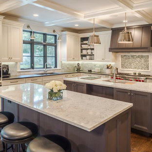 Huge traditional kitchen inspiration - Example of a huge classic l-shaped dark wood floor and brown floor kitchen design in Chicago with an undermount sink, quartz countertops, stainless steel appliances, two islands, recessed-panel cabinets, white cabinets, multicolored backsplash and mosaic tile backsplash