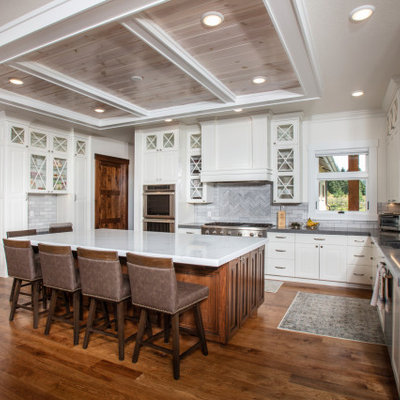 Inspiration for a transitional u-shaped dark wood floor and brown floor kitchen remodel in Other with an undermount sink, raised-panel cabinets, white cabinets, gray backsplash, stainless steel appliances, an island and gray countertops