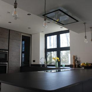 Пример оригинального дизайна: п-образная кухня-гостиная среднего размера в стиле модернизм с полуостровом, врезной раковиной, плоскими фасадами, серыми фасадами, столешницей из акрилового камня, серым фартуком, черной техникой, полом из керамической плитки, фартуком из кварцевого агломерата, серым полом, серой столешницей и кессонным потолком