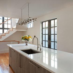 Immagine di una cucina minimalista di medie dimensioni con lavello sottopiano, ante lisce, ante marroni, top in quarzite, parquet chiaro, isola e pavimento marrone