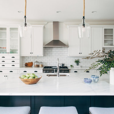 Galley kitchen photo in DC Metro with an undermount sink, shaker cabinets, white cabinets, white backsplash, subway tile backsplash, stainless steel appliances, an island and white countertops