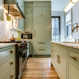 Diseño de cocina en L, clásica renovada, de tamaño medio, con fregadero integrado, armarios con paneles lisos, puertas de armario verdes, encimera de cuarcita, electrodomésticos de acero inoxidable, suelo de madera clara, una isla y suelo marrón