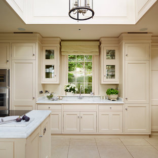 Inspiration for a large traditional kitchen/diner in London with beaded cabinets, marble worktops, grey splashback, stainless steel appliances and an island.