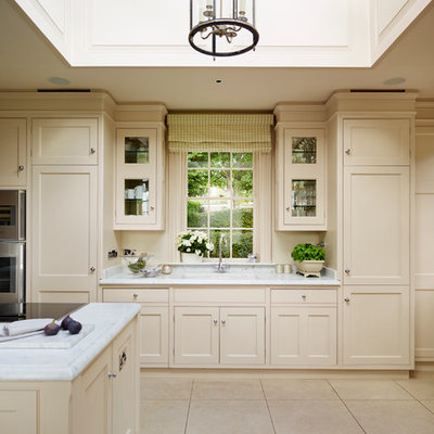 Eat-in kitchen - large traditional eat-in kitchen idea in London with beaded inset cabinets, marble countertops, gray backsplash, stainless steel appliances and an island