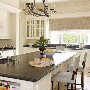 ニューヨークのトラディショナルスタイルのおしゃれなキッチン (アンダーカウンターシンク、シェーカースタイル扉のキャビネット、白いキャビネット、ベージュキッチンパネル、サブウェイタイルのキッチンパネル、ベージュの床) の写真