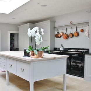 Idee per una cucina lineare tradizionale di medie dimensioni con ante con riquadro incassato, ante grigie, isola e pavimento giallo