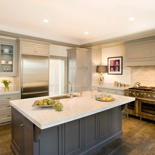 Example of a classic kitchen design in Boston with stainless steel appliances, a single-bowl sink, glass-front cabinets, gray cabinets and beige backsplash