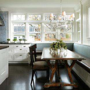 Пример оригинального дизайна: кухня в классическом стиле с обеденным столом, фасадами в стиле шейкер, белыми фасадами и синим фартуком