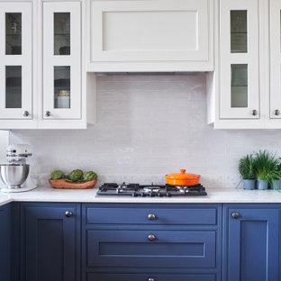 Klassische Wohnküche in U-Form mit Kassettenfronten, blauen Schränken, Küchenrückwand in Weiß, Halbinsel, weißer Arbeitsplatte, Quarzit-Arbeitsplatte und Rückwand aus Keramikfliesen in Sonstige