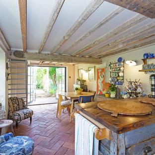 Esempio di una cucina rustica di medie dimensioni con isola e pavimento rosso